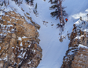 Bryce Newcomb drops a monster cliff air in the Teton backcountry near Jackson Hole Mountain Resort in Teton Village, Wyoming.
